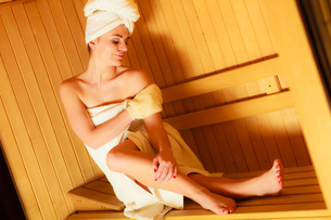 woman relaxing in wooden sauna roomの写真素材 [FYI00768937]