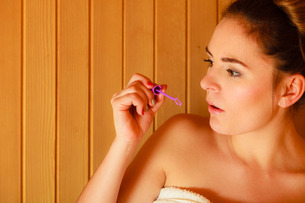 woman relaxing in a sauna room blowing soap bubblesの写真素材 [FYI00768940]
