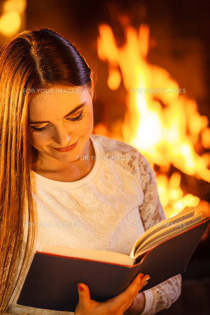 woman reading book at fireplace. winter home,relaxの写真素材 [FYI00768945]