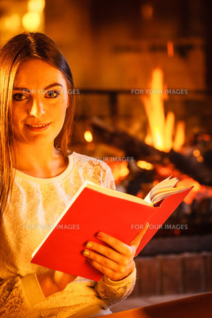 woman reading book at fireplace. winter home,relaxの写真素材 [FYI00768947]