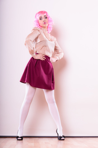 portrait woman with pink wig creative visage makeup posing on gray backgroundの写真素材 [FYI00768958]