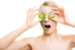 skin care. woman in clay mask with kiwi on faceの写真素材 [FYI00768964]