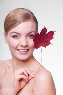 skin care. portrait of young woman girl with red maple leaf.の写真素材 [FYI00768982]