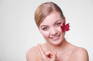 skin care. face of young woman girl with red maple leaf.の写真素材 [FYI00768983]