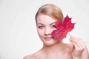 skin care. portrait of young woman girl with red maple leaf.の写真素材 [FYI00768984]
