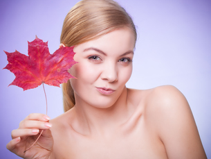 skin care. portrait of young woman girl with red maple leaf.の写真素材 [FYI00768985]