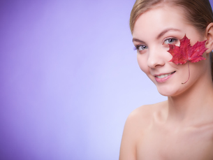 skin care. portrait of young woman girl with red maple leaf.の写真素材 [FYI00768987]