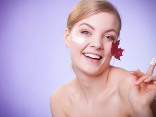 skin care. face of young woman girl with red maple leaf.の写真素材 [FYI00768991]