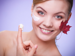 skin care. face of young woman girl with red maple leaf.の写真素材 [FYI00768993]
