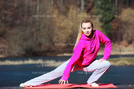 woman teenage girl in tracksuit doing exercise on pier outdoorの写真素材 [FYI00769062]