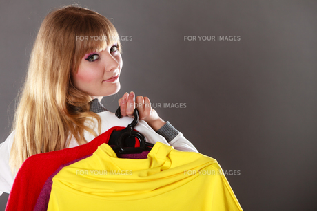 customer woman holding hangers with clothesの写真素材 [FYI00769099]