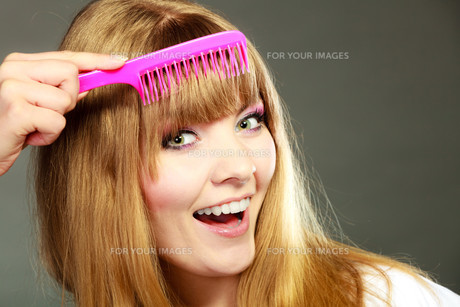 closeup of a woman combing her fringe with pink combの素材 [FYI00769101]