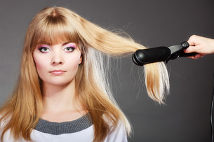 woman making hairstyle with hair ironの写真素材 [FYI00769103]