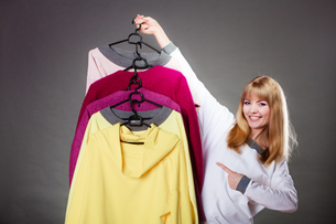 customer woman holding hangers with clothesの写真素材 [FYI00769112]