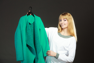 fashionable woman holding a green coatの写真素材 [FYI00769114]