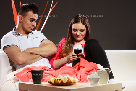 couple using mobile phone texting messagesの素材 [FYI00769153]