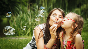 mother and little girl blowing soap bubbles in park.の写真素材 [FYI00769327]