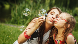 mother and little girl blowing soap bubbles in the park.の写真素材 [FYI00769334]