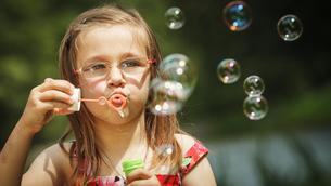 little girl having fun blowing soap bubbles in the park.の写真素材 [FYI00769336]