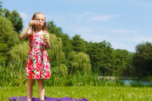 little girl having fun blowing soap bubbles in park.の写真素材 [FYI00769338]