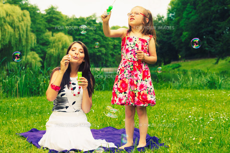 mother and child blowing soap bubbles outdoors.の写真素材 [FYI00769339]