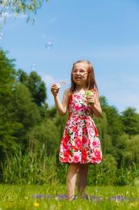 little girl having fun blowing soap bubbles in park.の写真素材 [FYI00769340]