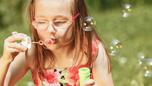 little girl having fun blowing soap bubbles in the park.の写真素材 [FYI00769342]