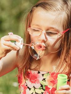 little girl having fun blowing soap bubbles in park.の写真素材 [FYI00769343]