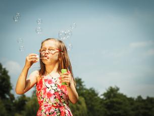 little girl having fun blowing soap bubbles in the park.の写真素材 [FYI00769346]