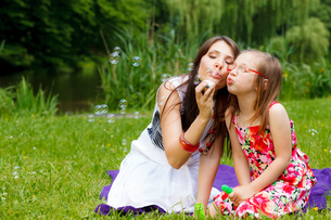 mother and little girl blowing soap bubbles in the park.の写真素材 [FYI00769350]
