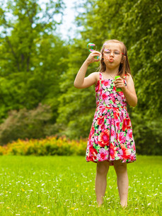little girl child blowing soap bubbles outdoor.の写真素材 [FYI00769361]