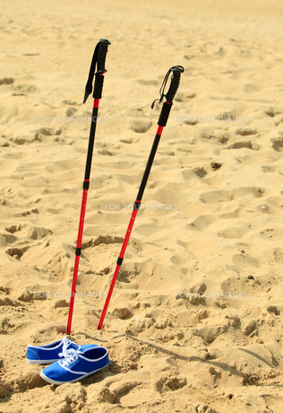 nordic walking. sticks and violet shoes on a sandy beachの素材 [FYI00769371]