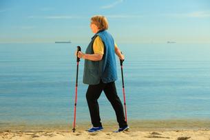 active senior woman nordic walking on a beachの素材 [FYI00769374]