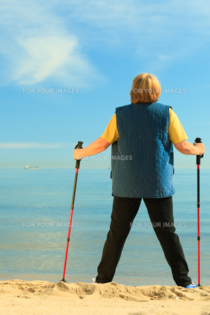 active senior woman nordic walking on a beach. from behindの素材 [FYI00769376]