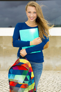 A beautiful student in the college holding a backpak and notebooksの写真素材 [FYI00769483]