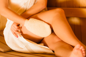 closeup of woman in sauna with exfoliating glove.の写真素材 [FYI00769754]