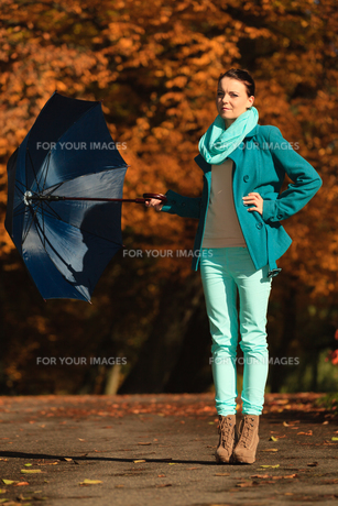 girl walking with blue umbrella in autumnal parkの素材 [FYI00769970]