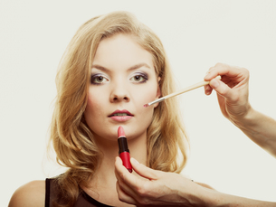 makeup. woman applying red lipstick with brushの写真素材 [FYI00769994]