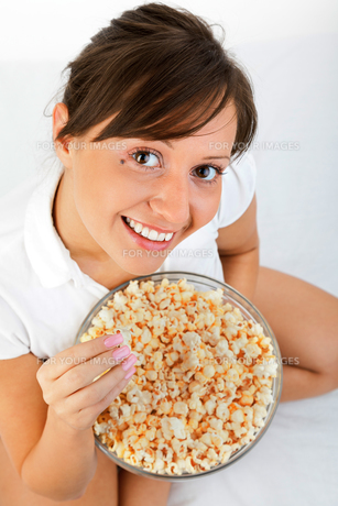 Young woman eating popcornの写真素材 [FYI00770171]