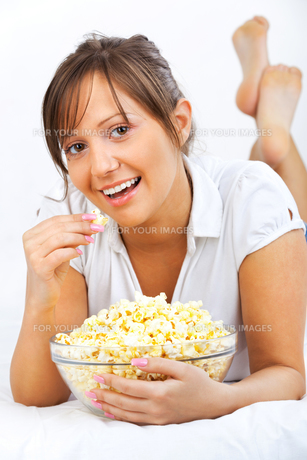 Young woman eating popcornの写真素材 [FYI00770175]