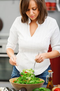 Young woman making saladの写真素材 [FYI00770186]