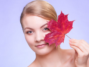skin care. portrait of young woman girl with red maple leaf.の写真素材 [FYI00770441]