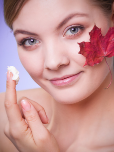 skin care. face of young woman girl with red maple leaf.の写真素材 [FYI00770442]
