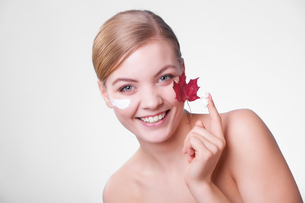 skin care. face of young woman girl with red maple leaf.の写真素材 [FYI00770463]
