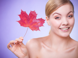 skin care. portrait of young woman girl with red maple leaf.の写真素材 [FYI00770467]