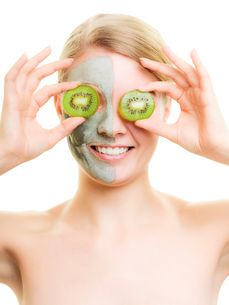 skin care. woman in clay mask with kiwi on faceの写真素材 [FYI00770471]