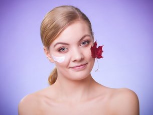 skin care. face of young woman girl with red maple leaf.の写真素材 [FYI00770483]