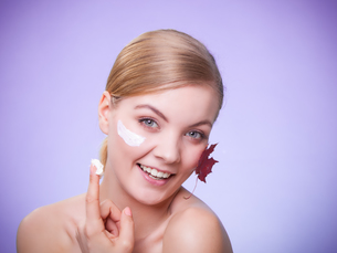 skin care. face of young woman girl with red maple leaf.の写真素材 [FYI00770490]
