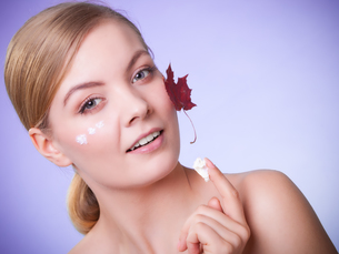 skin care. face of young woman girl with red maple leaf.の写真素材 [FYI00770492]