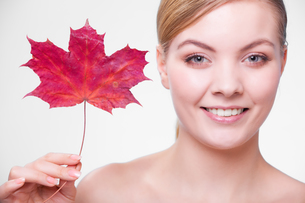 skin care. portrait of young woman girl with red maple leaf.の写真素材 [FYI00770500]